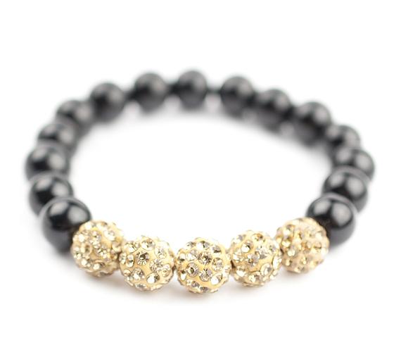 Az ébenfekete gyöngysort öt gyönyörűen csillogó, apró, aranyszín cseh kristállyal kirakott gömb díszíti. Az arany és fekete összhangja egy különleges, elegáns darabot teremt. Ára: 1490 forint.