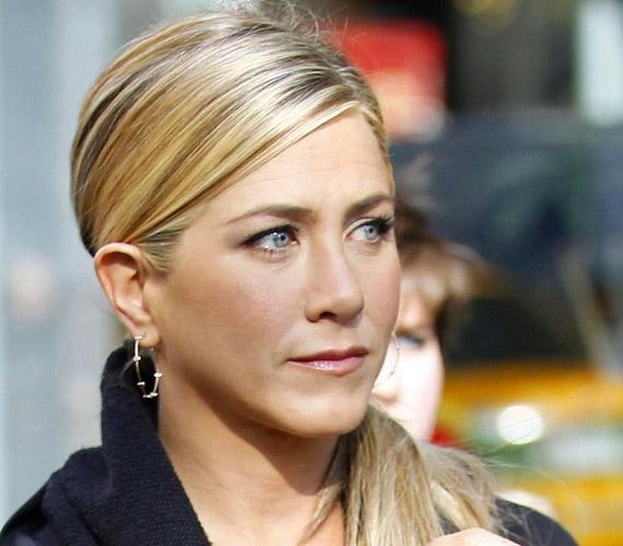 Oldalra fésült, lenyalt frizura, mely kissé szigorú, de jól áll Jennifernek.