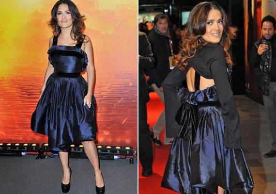 Az YSL koktélruháját a kivágott hátrész teszi izgalmasabbá, a két fekete szalag pedig nemcsak karcsúbbnak, de magasabbnak is mutatja a színésznőt, míg a fodrok a dekoltázsra terelik a figyelmet.