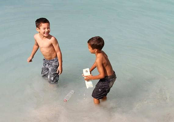 Kisgyerekek játszanak a vízben úszkáló szeméttel.