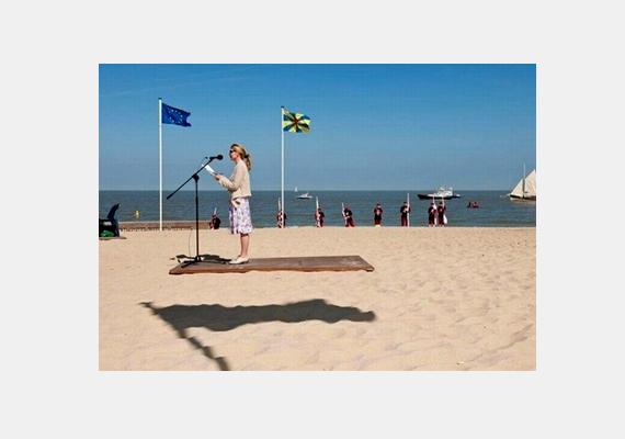 Elsőre úgy tűnik, mintha a lány egy lebegő szőnyegen tartana beszédet. A csalafinta árnyék azonban egy zászlóhoz tartozik.
