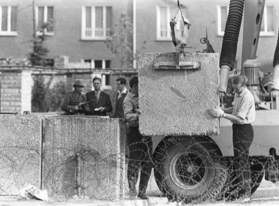 A nyugati oldalról készítették ezt a felvételt, amin az NDK néphadseregének katonája is szerepel, géppuskával a kezében. A képen a berlini fal építési munkálatait végzik, az előtérben még látszanak a korábban kihúzott szögesdrótkerítés maradványai.