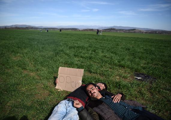"""Afgán migránsok a görög oldalon, kartonlapjukon az """"OPEN"""" felirattal. A macedón-görög határt február 21-én zárták le előttük."""