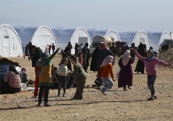 Gyerekek játszanak a táborban, megfeledkezve a környezetről.
