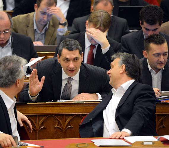 Eközben Orbán Viktor miniszterelnök, Lázár János államtitkár és Semjén Zsolt miniszterelnök-helyettes nevetgél a Parlamentben.
