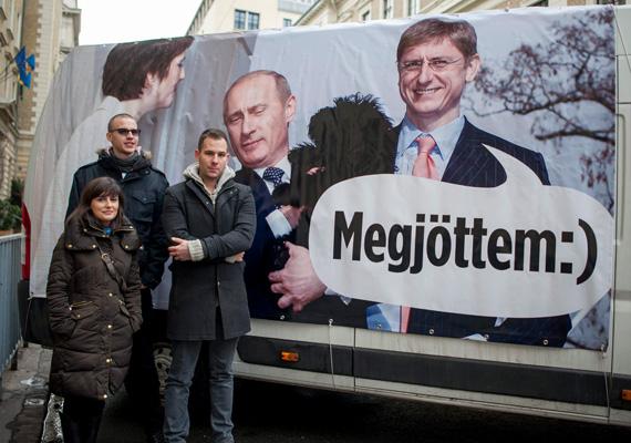 Palócz László, Simon Beatrix és Falusi Vajk áll egy furgon oldalára erősített molinó előtt. A képek Gyurcsány Ferencet, feleségét Dobrev Klárát, illetve Vlagyimir Putyint közösen ábrázolták, a volt miniszterelnök azt mondja egy szóbuborékban: megjöttem. Ugyanakkor az autóra szerelt hangszórókból az őszödi beszéd szólt.