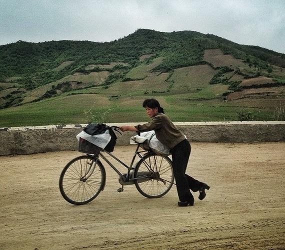 """""""Egy nő egy vidéki földúton tolja a biciklijét,Hamhung városának közelében."""""""