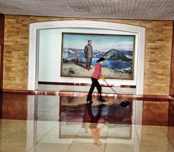"""""""Egy észak-koreai nő mossa a padlót a néha vezér,Kim Ir Szen portréja előtt, Hamhungban."""""""
