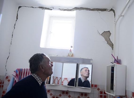 Hajnal József a földrengés következtében megrongálódott lakását mutatja Tenken.