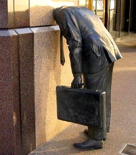 """A falba ragadt üzletemberAz ácsorgó üzletember-szobor, akinek a feje a falba """"szorult"""", az Ernst & Young Building előtt található Los Angelesben. Az alkotás bronzból készült."""