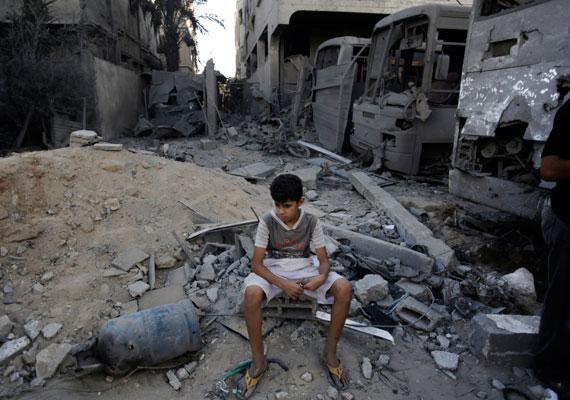 Fiatal fiú az utcán heverő törmelékek között. Az utakat sok helyen torlaszolják el a lerombolt épületek maradványai.