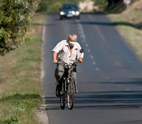 Egy évvel a katasztrófa után egészségügyi maszkot viselő férfi kerékpározik a vörösiszap sújtotta Devecser határában.