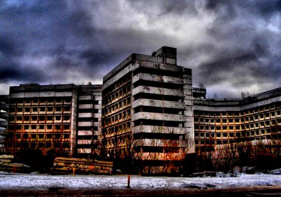 A kórház robusztus épületként emelkedik a város fölé.