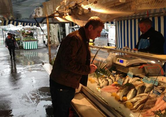 A volt miniszterelnök még csak ismerkedik a tengeri herkentyűkkel a lyoni piacon.