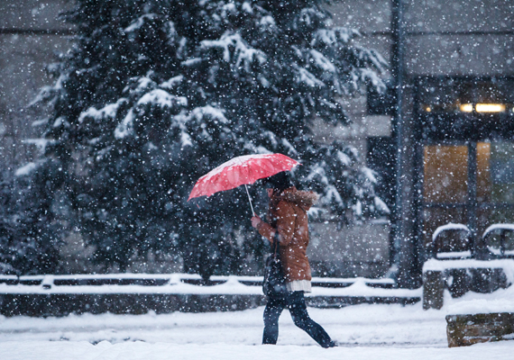 Gyalogos sétál a sűrű hóesésben Nagykanizsán.