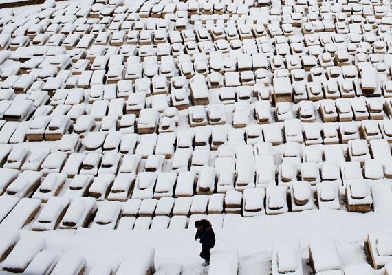 Férfi sétál a vastagon havas sírok között Jeruzsálemben.