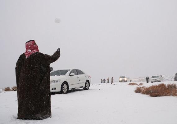 Egy szaúd-arábiai férfi hógolyózik az országot elért hóviharban.