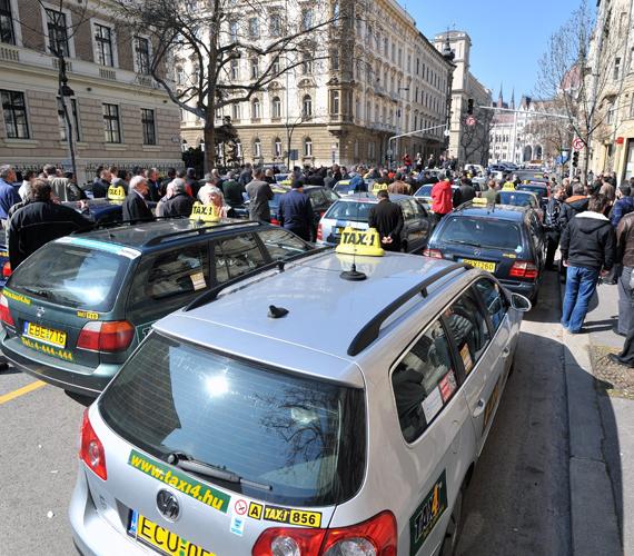 Az Országos Taxis Szövetség és a Taxi Gépkocsivezetők Független Szakszervezetének közös figyelemfelhívó demonstrációja Budapesten, az Alkotmány utcában. Elfogadhatatlannak tartják, hogy a fővárosi közgyűlés fix tarifa helyett a maximált hatósági ár emelését akarja.