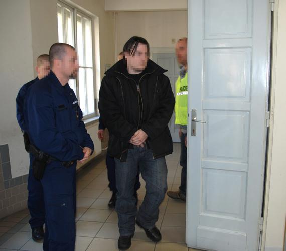 A kényszervallatás és halált okozó testi sértés gyanúja miatt őrizetbe vett két izsáki rendőr egyikét vezetik elő az előzetes letartóztatásról döntő ülésre a Kecskeméti Városi Bíróság folyosóján.