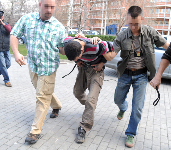 Rendőrök viszik be azt a férfit, aki bevallotta, hogy április 7-én hajnalban megölte Király Tamás divattervezőt.