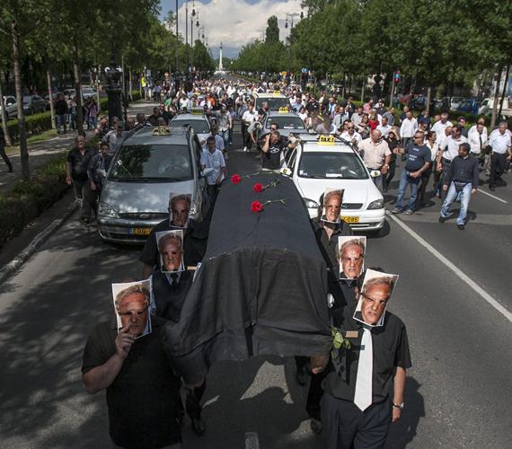 """A résztvevők - arcuk előtt Komáromi Endrének, a Fővárosi Taxiállomásokat Üzemeltető Szolgáltató Nonprofit Kft. ügyvezetőjének fotójával - """"jelképesen eltemetve hivatásukat"""" egy fekete koporsót vittek a vállukon."""