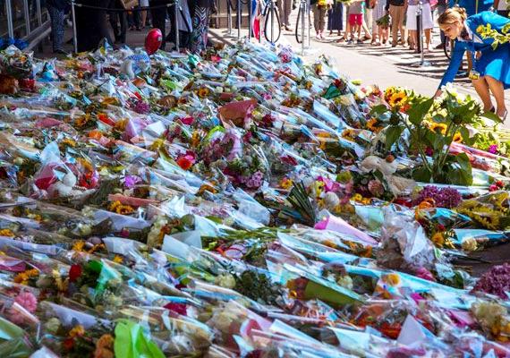 Gyászolók helyeznek el virágokat az amszterdami Schiphol repülőtér mellett.