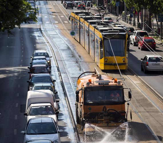 Fővárosi Közterület-fenntartó Zrt. locsolóautója vízzel hűti a villamossíneket a Szent István körúton.