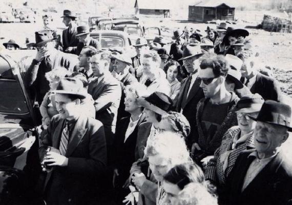 A fenti fotó a negyvenes években készült egy hídavatáson, és a Virtual Museum of Canada elnevezésű weboldalon található. Nemrégiben azonban valaki figyelmes lett egy apró részletre: a képen szereplő napszemüveges férfi ruházata egyáltalán nem illik oda, ráadásul mintha egy fényképezőgépet tartana a kezében.