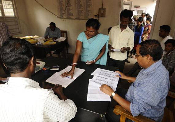 Indiai nő az egy hónapos szavazáson odanyomja ujjlenyomatát a névjegyzékre a voksolás előtt.