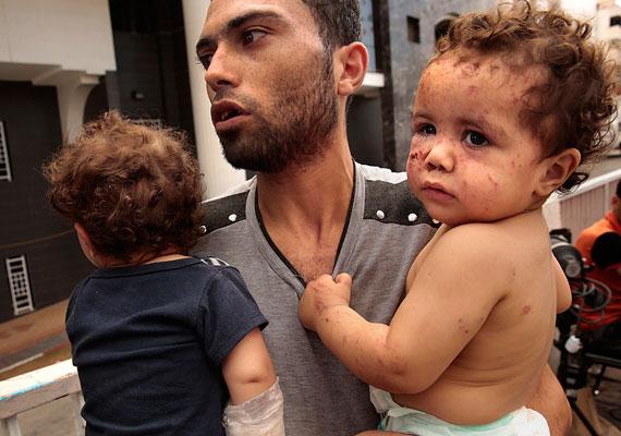 Apa érkezik meg egy gázai kórházba két gyermekével egy bombatámadás után. Az izraeli hadsereg a hónap elejétől múlt hét csütörtökig légitámadásokat hajtott végre, csak ez után kezdődtek meg a szárazföldi műveletek.