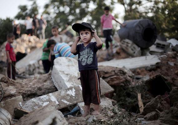 Palesztin kisfiú áll rémülten egykori lakóházuk romjain. Bár az izraeli hadsereg előre figyelmezteti a civileket, milyen célpontokra mér csapást, a sűrűn lakott területen nincs hova menekülni.