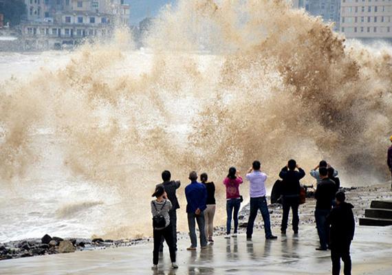 Sitangban bámészkodók fotózzák a partot elárasztó hatalmas hullámokat.