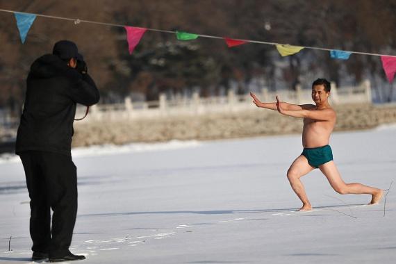 A Shenjang Pejling téliúszó-egyesület tagjai gondosan bemelegítettek, mielőtt a jeges vízbe ugrottak.