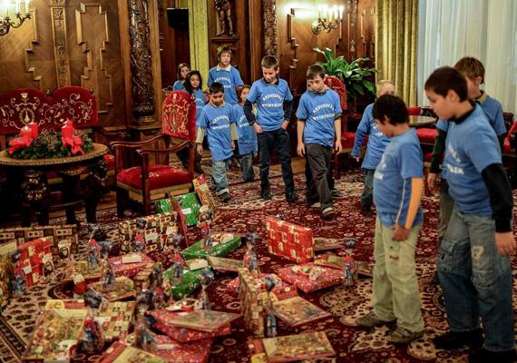 Az ajándékozás pillanata, a gyerekek ámulva nézik a meglepetéseket.