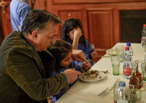 A miniszterelnök segít a Kedvesház egyik lakójának felvágni az ételt.