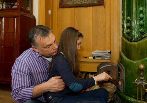 Apa és lánya begyújtják a cserépkályhát.