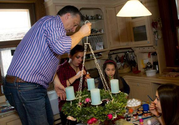 Beindul a családi előkészület a konyhában, Orbán Viktor az asztalra állva próbálja a húsvéti koszorút felszerelni a plafon gerendájára, a lányok kitartóan festik a tojásokat.
