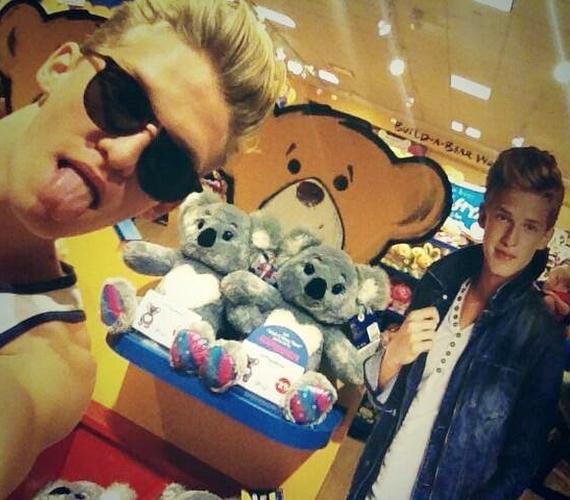 Így pózol Cody Simpson néhány mackóval és egy papír Cody Simpsonnal.