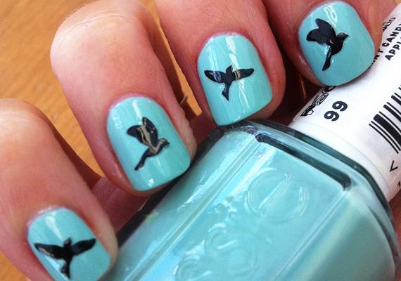 A madarak a szabadságot - jelen esetben a nyári szünetet - jelképezik. Ez a minta már valamivel könnyebb, hiszen a szimpla türkiz alapra körömlakktollal hamar rá lehet rajzolni a csiripelő tollasokat.