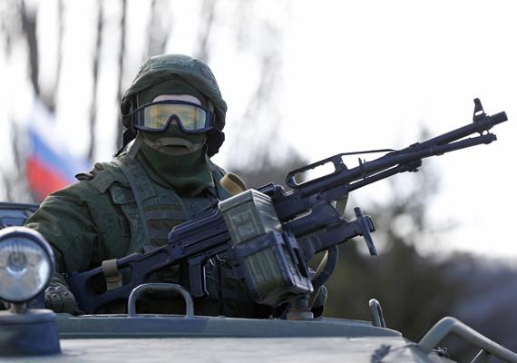 Fegyveres katona várakozik egy tankban.