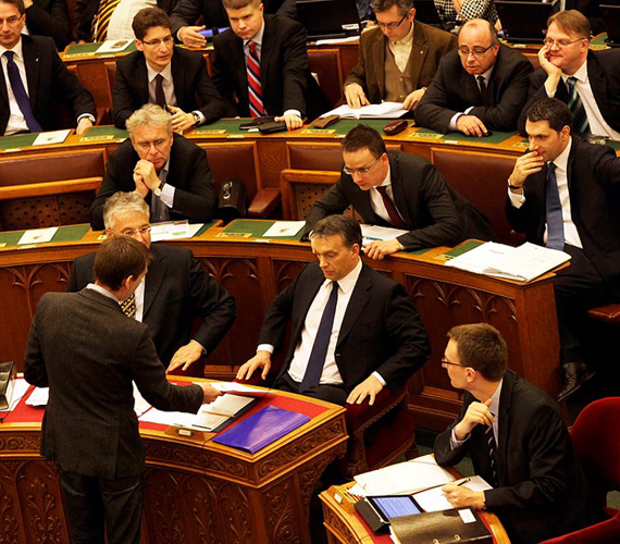 Jávor Benedek, az LMP frakcióvezetője átnyújtja Orbán Viktornak az aláírásgyűjtő ívet. A fideszesek feszülten figyelnek.