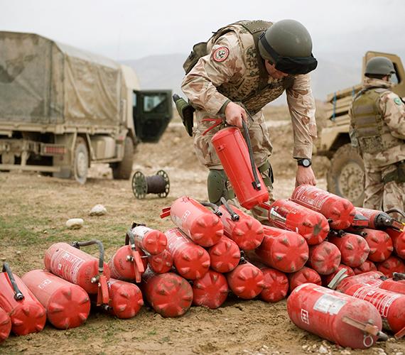 Poroltótartályokat pakol egy katona az afganisztáni Kilaghaj közelében.