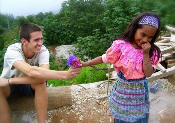 Egy turista virágot ad egy guatemalai kislánynak, akivel éppen most találkozott.