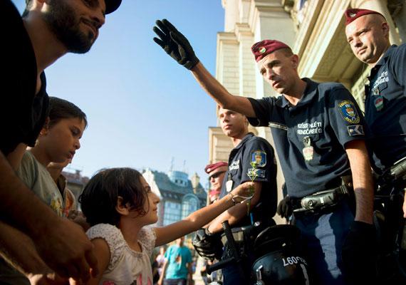 Egy kislány virágot próbál adni egy, a Keleti előtt posztoló rendőrnek. Rengeteg gyerek, köztük csecsemők is vannak a pályaudvar környékén. A legtöbb menekült a bizonytalanság és a hőség ellenére sem tűnt tegnap ingerültnek.