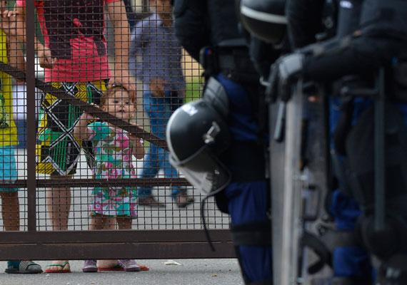 Nagyjából száz menekült kukákat gyújtott fel a túlzsúfolt debreceni menekülttáborban. A kiérkező rohamrendőröket figyeli egy, a táborban tartózkodó kislány anyukája mellől.
