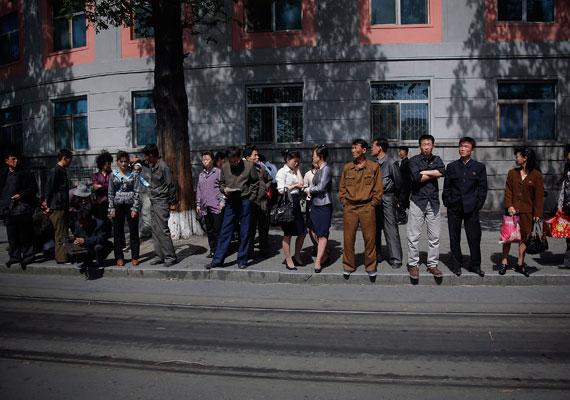 Trolibuszra várakoznak a fővárosban, Phenjanban. Azért öltözködnek ilyen hasonlóan az emberek, mert az országba külföldi termékek nem jutnak be, csak az állami termelővállalatok produktumai érhetőek el.