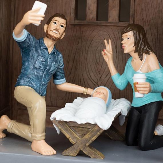 A kis Jézus mellett büszkén szelfizik a farmeringes József és a csücsörítő Mária, aki kezében papírpoharas kávét szorongat.