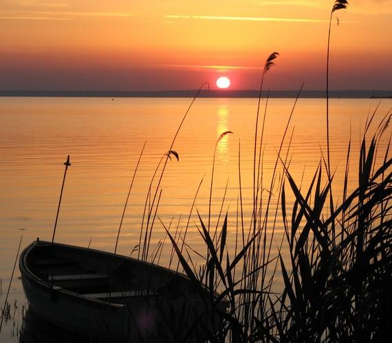 A balatoni naplemente egy tökéletes pillanata, amikor a napkorong még teljes egészében látszik a horizonton.