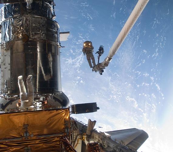 John Grunsfeld űrhajóst láthatod a képen a karhoz erősítve, míg társának, Andrew Feustelnek csak a lába kandikál ki.