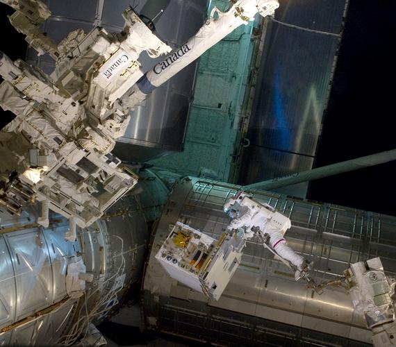 Mike Fossum űrhajós lábát az űrállomás távoli irányítórendszerének egyik karjához erősítették. A fotó 2011 júliusában készült.